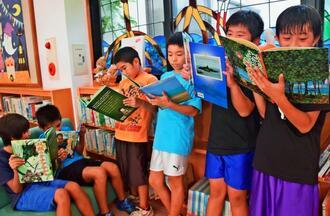 民話の絵本を読む児童たち=10月27日、金武町立図書館