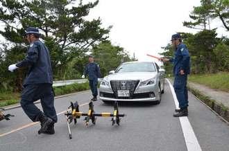 県道70号を通行止めにした警察官=10日午前9時半、東村高江