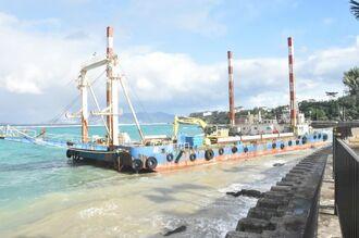 瀬底島南の海域から漂着した船=31日午前10時ごろ、恩納村名嘉真の海岸