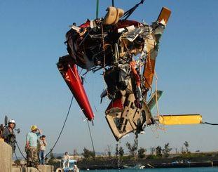 漁船で引かれ港に引き上げられる大破した遊覧ヘリ=2日午後3時50分ごろ、古宇利港(山城響撮影)