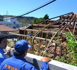 全壊した空き屋を視察する国や町の関係者=1日、与那国町祖納地区