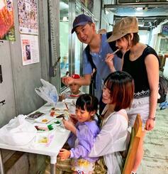 泊いゆまちの市場共用のテーブルで刺身を食べる外国人観光客=11日、那覇市泊