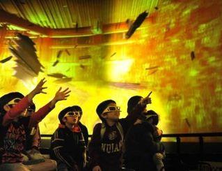 飛び出す映像をつかみとろうとするなど、楽しむ子どもたち=豊見城市の豊崎ライフスタイルセンターTOMITON