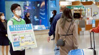 到着口前でPCR検査の案内板を持ち、乗客に検査案内を呼び掛けるスタッフ=3日、那覇空港