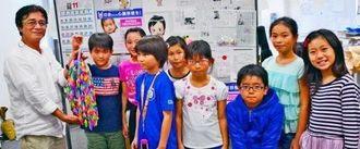 のあちゃんを元気づけたいと千羽鶴を贈った宮島君(左から2人目)ら城西小4年3組の児童たち=19日、那覇市・のあちゃんを救う会事務局