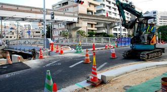 30日正午の久美橋開通に向けて、作業を進める工事関係者=29日午後5時前、那覇市久茂地