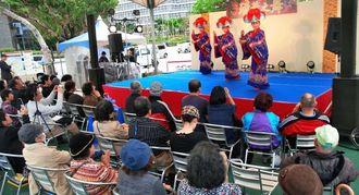 琉球舞踊を見学する観光客=2日、那覇市パレットくもじ前広場