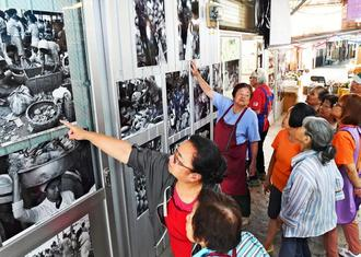 「あんやたん農連市場」の展示写真を見て、昔話に花を咲かせる市場の人たち=1日、那覇市樋川の農連市場(下地広也撮影)