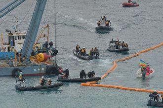 キャンプ・シュワブ沿岸でブイを設置する作業船(左)。抗議船(右)が近づき、周辺に海保のボートが警戒で集まった=28日午前10時11分、名護市辺野古