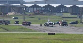嘉手納基地に緊急着陸した同基地所属のF15戦闘機。燃料を吹き出し地面がぬれているのが確認できる=29日午前9時53分、嘉手納基地