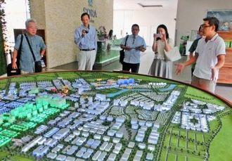 ベカメックス東急の担当者から新都心開発について説明を受けるアジア経済戦略構想策定委員会の富川盛武会長(左)、上地恵龍琉球大学客員教授(左から2人目)=ベトナム・ビンズン省