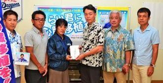 米須会長(右から3人目)から當山みゆき共同代表に寄付金が手渡された=2日、北谷町商工会
