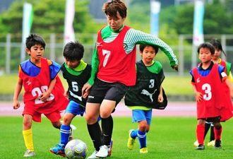 女子サッカー日本代表の岩清水梓選手(中央)とミニゲームを楽しむ子どもたち=南城市陸上競技場