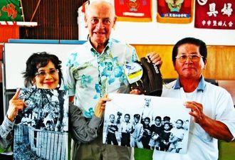 当時の写真とグローブを手に再会を喜ぶ横田政一さん(右)とリチャードさん(中央)=うるま市宇堅公民館