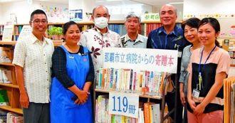 がん関連本119冊を前に、本を寄贈した市立病院と図書館の職員ら=9日午前、那覇市・牧志駅前ほしぞら図書館