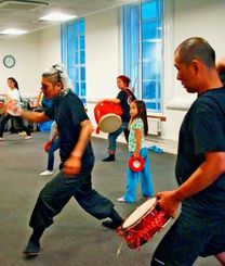 高橋大三さん(左)の指導を受けて、エイサーを学ぶロンドン沖縄三線会のメンバー=ロンドン大学東洋アフリカ学院内
