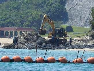 米軍キャンプ・シュワブの海岸に重機を使って石を敷く作業員=3日午後、名護市辺野古(下地広也撮影)