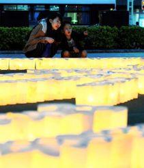 震災犠牲者を悼むキャンドルに足を止めて見つめる人たち=11日午後6時半ごろ、那覇市・パレットくもじ前(松田興平撮影)