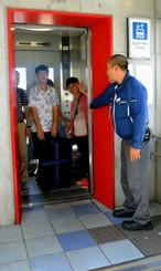 大きなスーツケースを抱え復旧したばかりのエレベーターを利用する外国人観光客と、メーカー職員(右)=21日、「ゆいレール」牧志駅