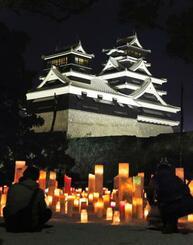 熊本地震の発生から5年を迎え、ライトアップされた熊本城の天守閣と加藤神社で火をともされたキャンドル=14日夜、熊本市