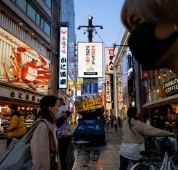 大阪・ミナミを行き交うマスク姿の人たち=18日午後6時29分