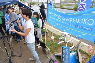 「NO BASE in HENOKO」の横断幕を掲げスピーチするシールズ琉球のメンバー=2015年11月14日、名護市辺野古のキャンプ・シュワブゲート前