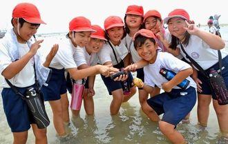 ニセクロナマコや二枚貝を見つけ喜ぶ港川小4年生=浦添市港川・カーミージー周辺