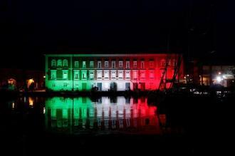 新型コロナウイルスの感染拡大食い止めを応援しようと、イタリア国旗の色にライトアップされた海軍基地施設=29日、ナポリ(ロイター=共同)