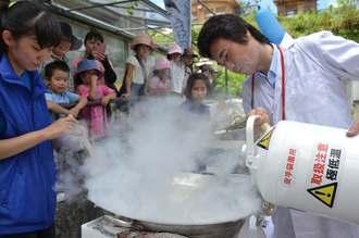 オレンジジュースが入った鍋に液体窒素を注ぐ高江洲博士(右)=15日、沖縄こどもの国