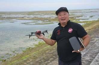 西海岸の海を背に、海外を共に旅してきたドローンを持つ橋本顕彰さん=5月28日、浦添市西洲