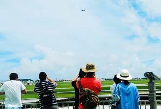 戦闘機の姿を追う中国人観光客=6日、嘉手納町屋良の道の駅かでな