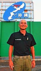 故郷の今帰仁村をアピールした看板の前で笑顔を浮かべる大城勝さん=茨城県古河市