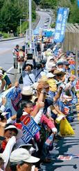 米軍キャンプ・シュワブゲート前で手をつなぐ「人間の鎖大行動」の参加者=22日午後2時36分、名護市辺野古(下地広也撮影)