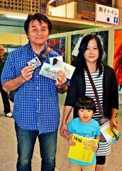来場者1万人目となり、記念品を持つ金城洋一さん(左)、直美さん(右)、琉神ちゃん=31日、浦添市民体育館