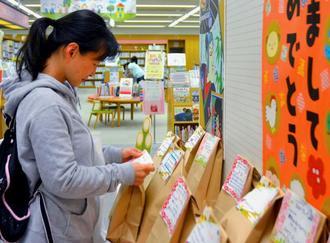 興味深そうに「本の福袋」を手にする利用者=5日、県立図書館