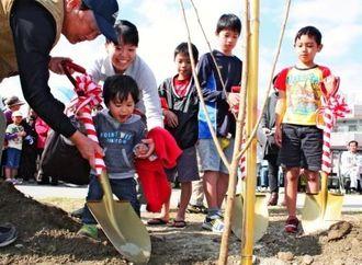 真嘉比遊水地の土手沿いに、平和のシンボル「陽光桜」を植える親子連れら=23日、那覇市真嘉比