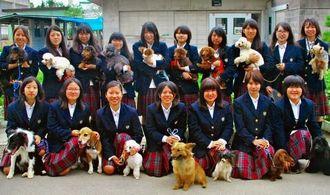 セラピー犬を育成する動物介在活動チーム。前列左から4頭目がひまわり=うるま市の中部農林高校