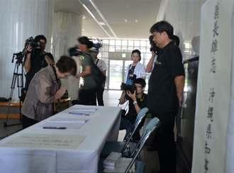 翁長雄志知事を追悼し、記帳後に手を合わせる女性(左)=10日午前、県庁