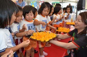 試食用の県産マンゴーをほおばる大地保育園の園児=15日、豊見城市・JAおきなわ食菜館「菜々色畑」