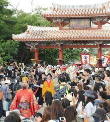 琉球王朝時代の栄華を再現し、きらびやかな衣装で練り歩いた「古式行列」=3日午後2時前、那覇市・首里城公園