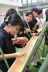 流しそうめんの要領で、楽しみながら沖縄そばを味わう生徒ら=八重山農林高校