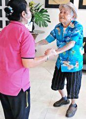 介護スタッフの仲村智子さんにマンボのステップを教える森茂吉さん(右)=18日、糸満市兼城