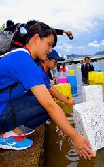 平和への願いを込め、灯籠流しをする北谷高校生=6日、広島市の元安川