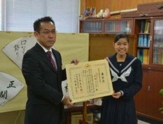 母の知人から譲り受けた制服で表彰状を受け取る平田こころさん(右)=石垣第二中学校
