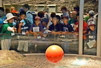 ガイド(左)の話を聞きながら爆心地の模型を見る糸満市の子どもたち=広島市・広島平和記念資料館