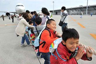 旅客機を相手に綱引きをする子どもたち=6日午後、那覇空港