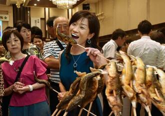 「清流めぐり利き鮎会」でアユの塩焼きを食べる参加者=13日午後、高知市