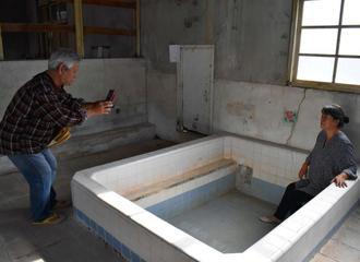 湯船跡に座る女性を撮影する嘉陽さん(左)