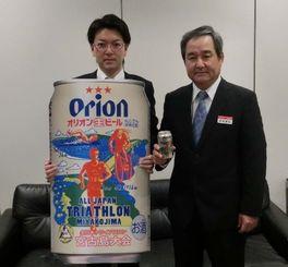 トライアスロンのデザイン缶をPRする伊波部長(右)と山城さん=沖縄タイムス社