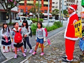 サンタクロースの服を着て子どもたちの登校を見守る新垣浩史さん=7日、浦添市屋富祖